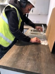 Photo of Darren in PPE repairing a work surface.