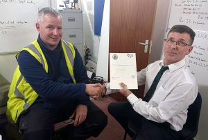 A construction worker receiving his onsite assessment NVQ certificate from his assessor.