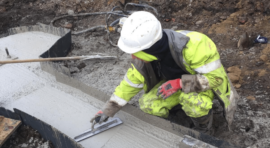 A groundworker in Hi-Vis jacket and hard hat working on a concrete foundation on a construction site during his NVQ Level 2 in Groundworks