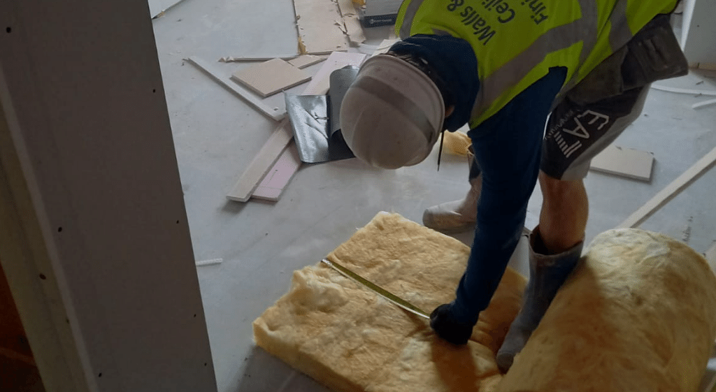 A worker measuring wool insulation during an observation for his Floor Insulation NVQ
