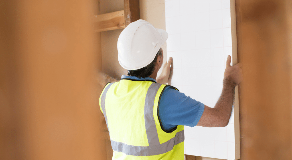 Example of Internal Insulation NVQ Level 2 assessment process: a worker installing an insulation board to an internal wall.
