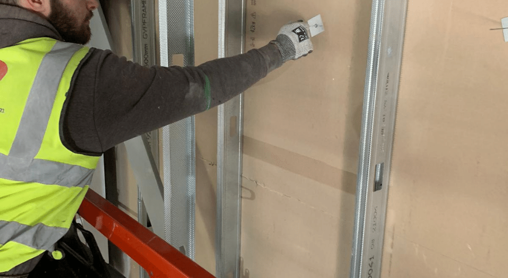 A dry liner fixing a plasterboard to a metal stud wall dry lining partition system while being assessed for his NVQ Level 2.